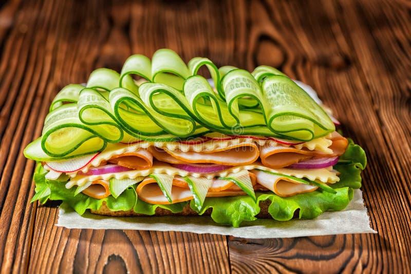 Πλούσιο σάντουιτς με το ζαμπόν, τυρί, μπέϊκον, ραδίκι, μαρούλι, αγγούρι στοκ φωτογραφία με δικαίωμα ελεύθερης χρήσης