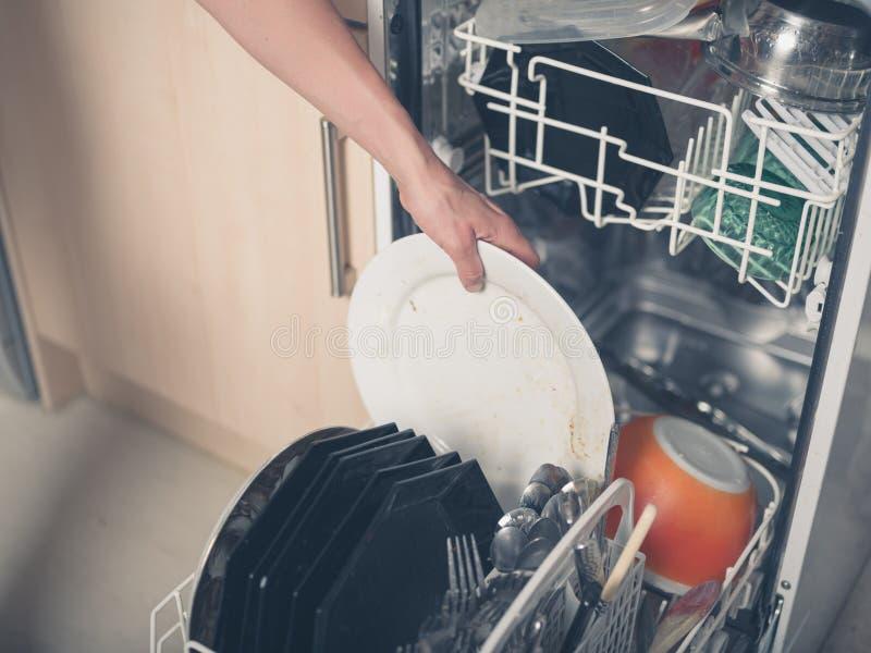 Πλυντήριο πιάτων φόρτωσης χεριών στοκ εικόνες