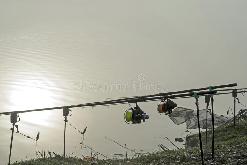 Ράβδος αλιείας κυπρίνων με μια σπείρα στο πρώτο πλάνο και ένας συναγερμός δαγκωμάτων στο υπόβαθρο της αντανάκλασης στο νερό στοκ φωτογραφία με δικαίωμα ελεύθερης χρήσης