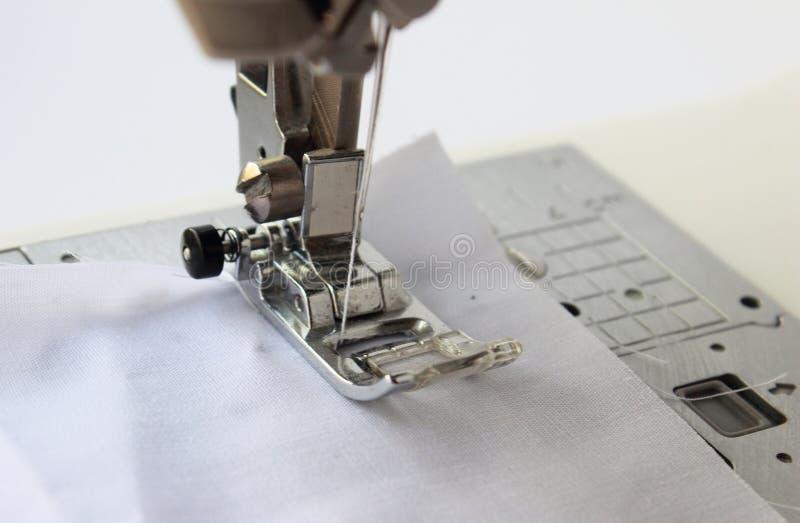 ράβοντας μηχανή με το ύφασμα που απομονώνεται στο άσπρο υπόβαθρο στοκ φωτογραφία με δικαίωμα ελεύθερης χρήσης