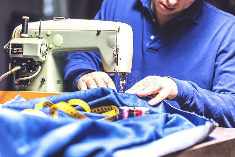 Ράβοντας τζιν τζιν με τη ράβοντας μηχανή Τζιν επισκευής από τη ράβοντας μηχανή Τζιν αλλαγής, που στριφώνουν ένα ζευγάρι των τζιν, στοκ φωτογραφία