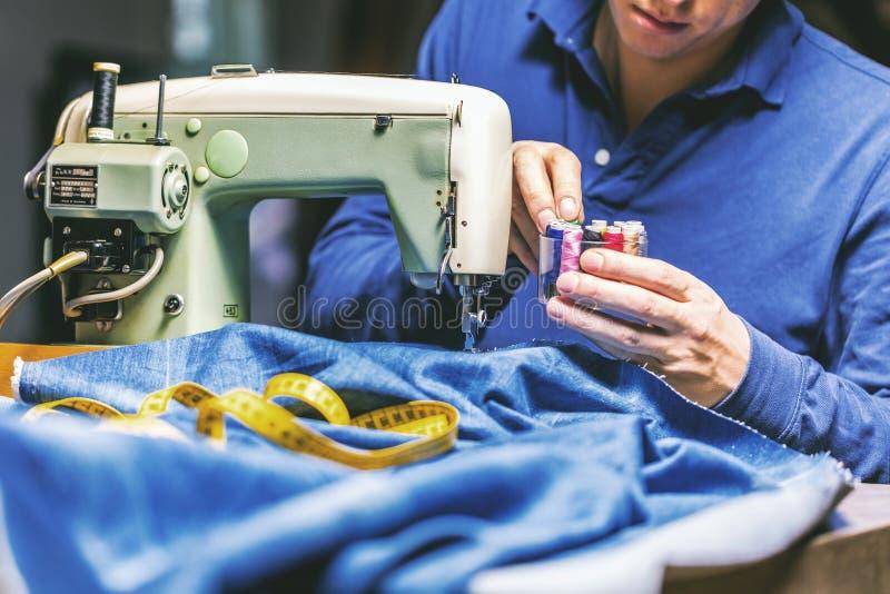 Ράβοντας τζιν τζιν με τη ράβοντας μηχανή Τζιν επισκευής από τη ράβοντας μηχανή Τζιν αλλαγής, που στριφώνουν ένα ζευγάρι των τζιν, στοκ εικόνες