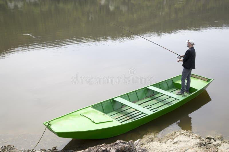 Ράβδος αλιείας εκμετάλλευσης αθλητικών ψαράδων και αλιεία από την πράσινη βάρκα στοκ εικόνες