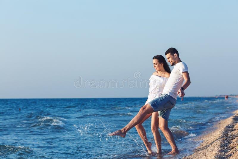Ράντισμα διασκέδασης αγοριών και κοριτσιών στη θάλασσα στοκ εικόνα