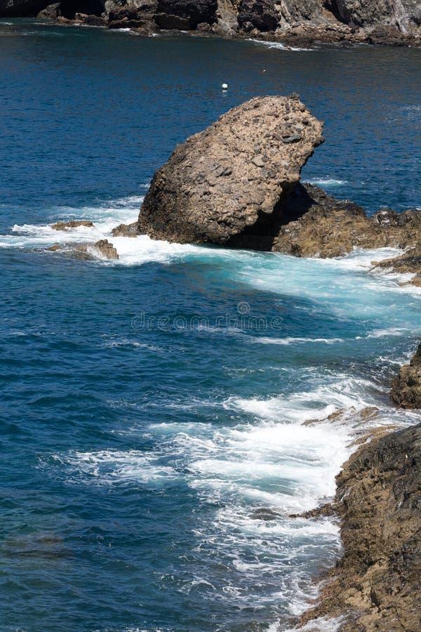 Ράντισμα κυμάτων πέρα από έναν βράχο στην παραλία Caleta Negra σε Ajuy σε Fuerteventura στοκ εικόνα