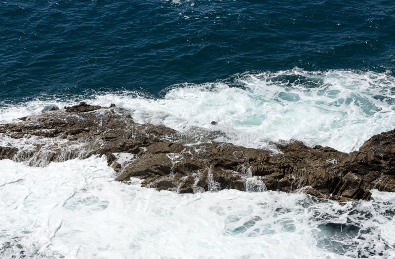 Ράντισμα κυμάτων πέρα από έναν βράχο στην παραλία Caleta Negra σε Ajuy σε Fuerteventura στοκ εικόνες