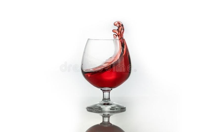 Ράντισμα κόκκινου κρασιού από ένα γυαλί, που απομονώνεται στο λευκό στοκ εικόνες