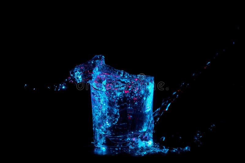Ράντισμα νερού από ένα γυαλί βράχων κάτω από το ανοιχτό μπλε και κόκκινα φώτα που απομονώνονται σε ένα μαύρο υπόβαθρο στοκ εικόνα