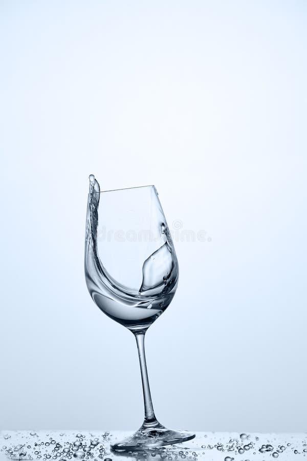 Ράντισμα νερού από γαρμένο wineglass με το καθαρότερο νερό στεμένος στο γυαλί στο ελαφρύ κλίμα στοκ φωτογραφία με δικαίωμα ελεύθερης χρήσης