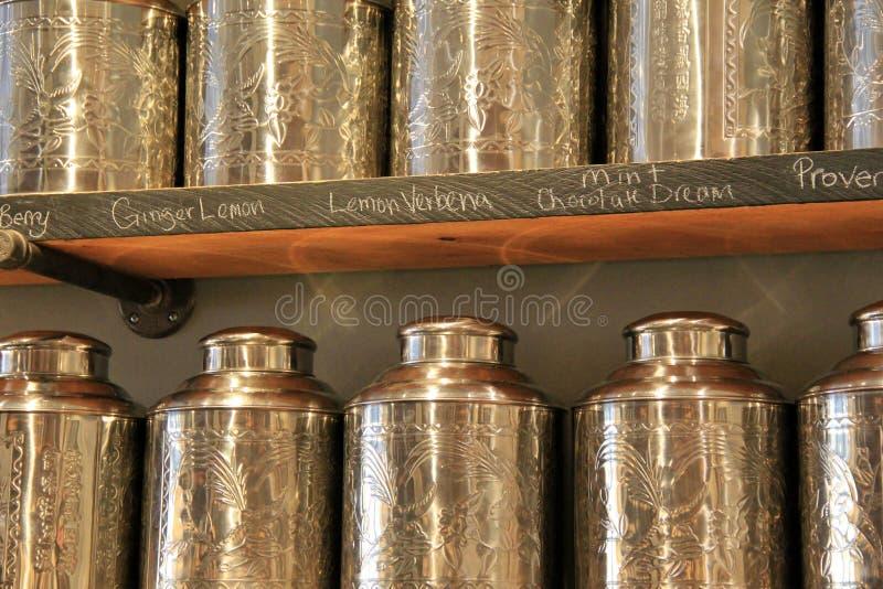 Ράφια με τα μεταλλικά κουτιά κασσίτερου και τα αρωματικά τσάγια στοκ εικόνες με δικαίωμα ελεύθερης χρήσης