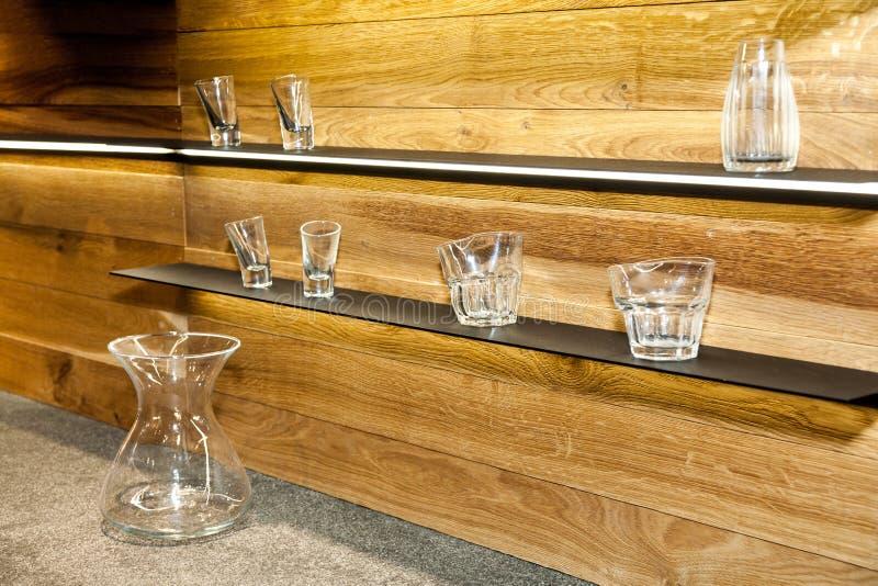 Ράφια με τη συλλογή των διακοσμητικών γυαλιών στο ξύλινο υπόβαθρο τοίχων στοκ φωτογραφία