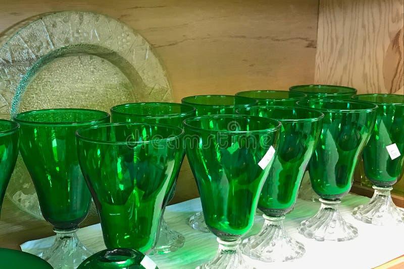 Ράφια των χρησιμοποιημένων πράσινων γυαλιών stemware thrift στο κατάστημα στοκ εικόνα με δικαίωμα ελεύθερης χρήσης