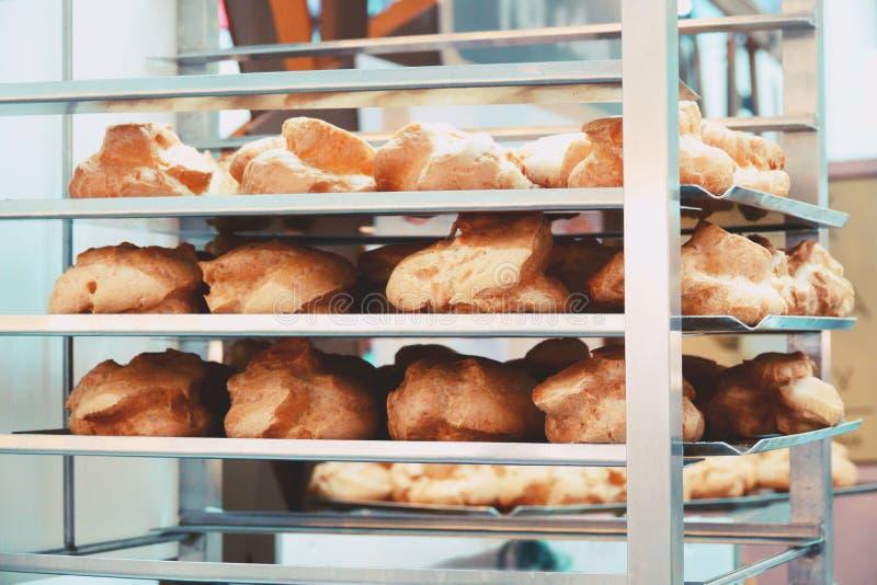 Ράφι αρτοποιείων με την κρέμα Choux στο κατάστημα αρτοποιείων στοκ εικόνα