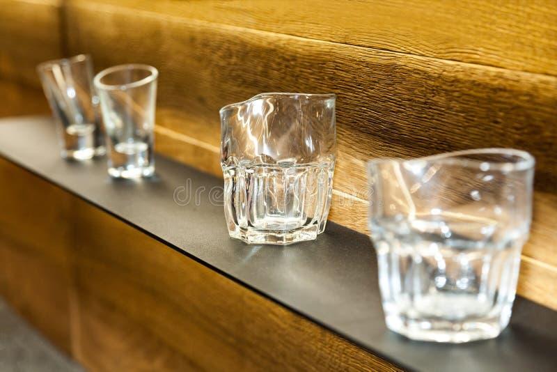Ράφι με τη συλλογή των διακοσμητικών γυαλιών στο ξύλινο υπόβαθρο τοίχων στοκ εικόνες με δικαίωμα ελεύθερης χρήσης