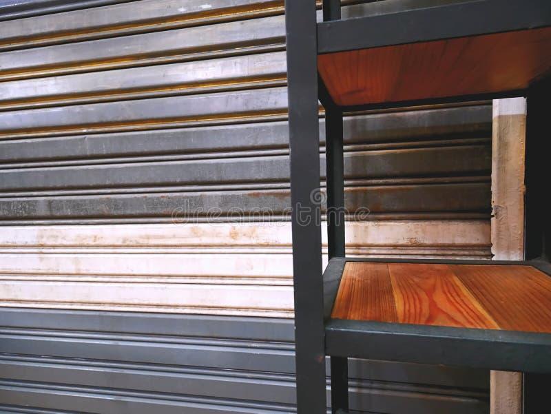 Ράφι μπροστά από την πτυσσόμενη ζαρωμένη πόρτα μετάλλων στοκ φωτογραφία με δικαίωμα ελεύθερης χρήσης