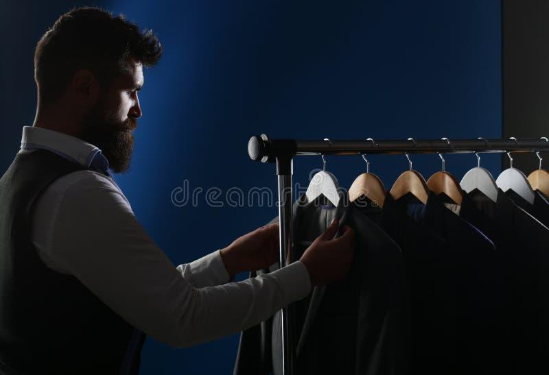 Ράφτης, προσαρμογή Κοστούμι ατόμων, ράφτης στο εργαστήριό του Κομψά ανθρώπινα κοστούμια που κρεμούν σε μια σειρά Κλασικά κοστούμι στοκ εικόνα
