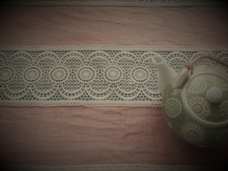 Ράχες πράσινες με άσπρο teapot στο ροδαλό υπόβαθρο στοκ εικόνα
