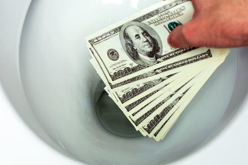 Ρίχνει τους λογαριασμούς δολαρίων στην τουαλέτα στοκ φωτογραφία με δικαίωμα ελεύθερης χρήσης