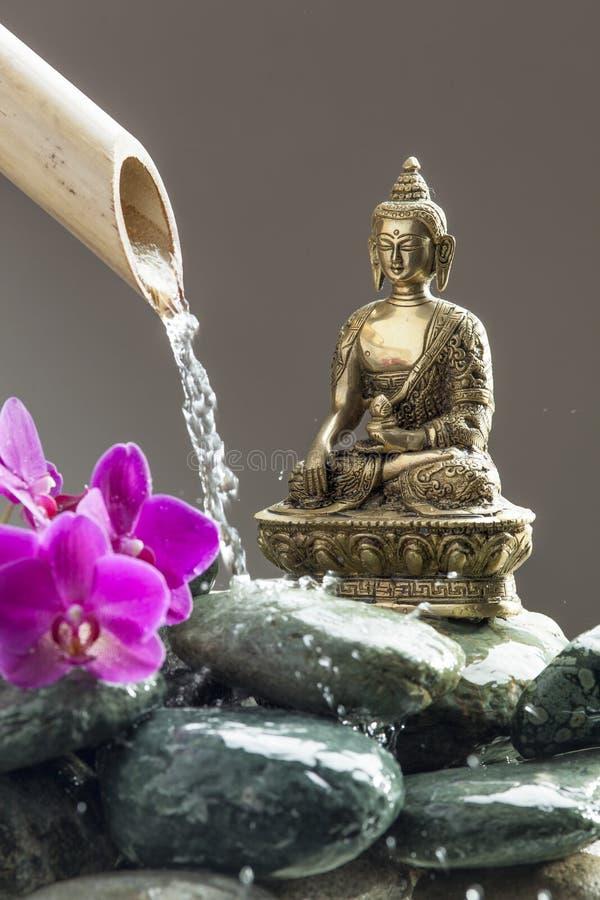 Ρίψη του νερού χαλάρωσης δίπλα στο Βούδα στοκ εικόνες