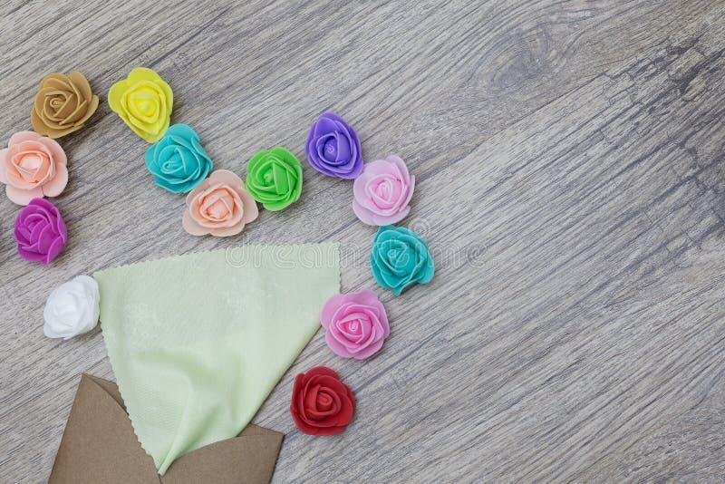 Ραβδιά βεραμάν πετσετών από το φάκελο τεχνών Διακοσμημένος στη μορφή της καρδιάς με τα πολύχρωμα τριαντάφυλλα επίπεδος βάλτε την  στοκ εικόνες με δικαίωμα ελεύθερης χρήσης