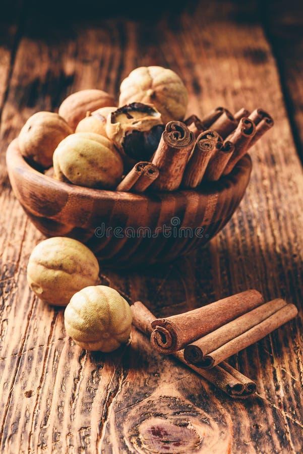 Ραβδιά κανέλας και ξηροί ασβέστες στο ξύλινο κύπελλο στοκ φωτογραφίες