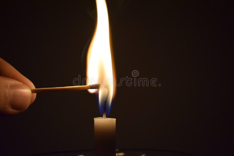 Ραβδί αντιστοιχιών που πιάνει την πυρκαγιά από το κάψιμο του κεριού στοκ εικόνα