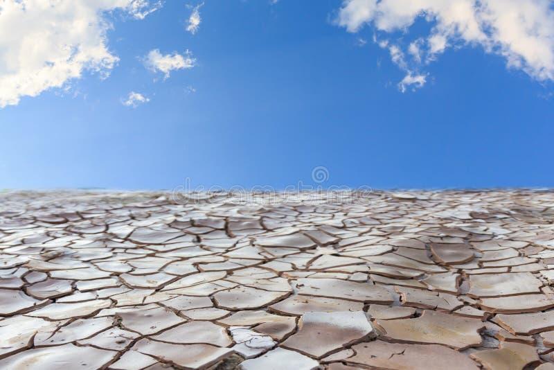 Ραγισμένο έδαφος με το μπλε ουρανό στοκ εικόνες