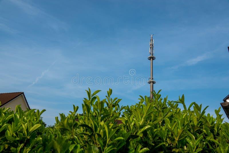 ραδιο ιστός για τους κινητούς πύργους τηλεφωνικών δικτύων επάνω από ένα κατοικημένο κτήριο στο μπλε ουρανό σε μια κατοικήσιμη περ στοκ εικόνες