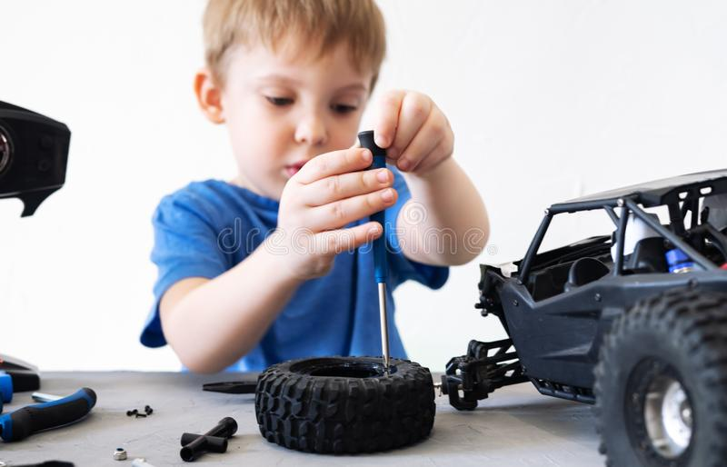 Ραδιόφωνο Obby που διαμορφώνει: ένα μικρό αγόρι σε μια μπλε μπλούζα που επισκευάζει ένα ραδιο-ελεγχόμενο αυτοκίνητο με λάθη με έν στοκ εικόνα με δικαίωμα ελεύθερης χρήσης