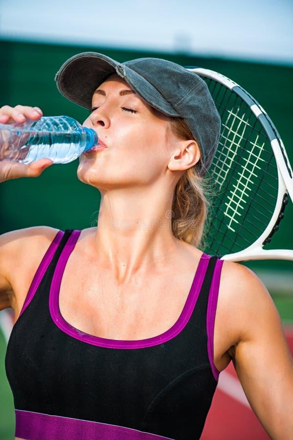 Ρακέτα εκμετάλλευσης γυναικών στο γήπεδο και το ποτό αντισφαίρισης στοκ φωτογραφίες