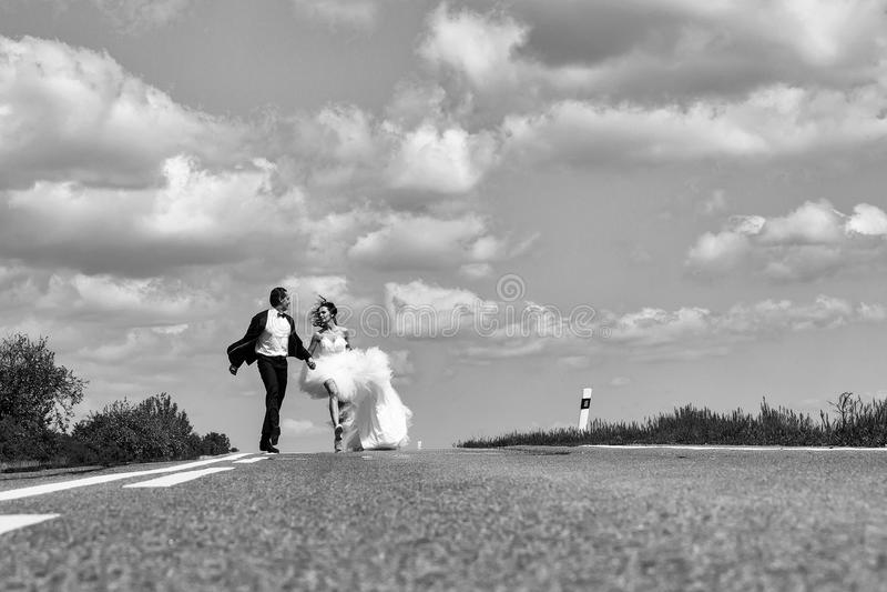 Ραντεβού στα τυφλά γαμήλιο ευτυχές ζεύγος που τρέχει στο δρόμο στοκ εικόνα