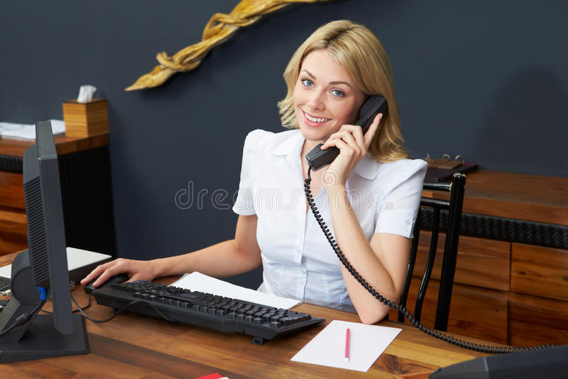 Ρεσεψιονίστ ξενοδοχείων που χρησιμοποιεί τον υπολογιστή και το τηλέφωνο στοκ φωτογραφία με δικαίωμα ελεύθερης χρήσης