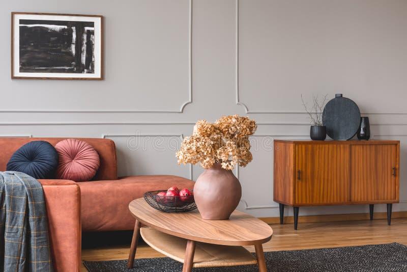 Ρετρό ξύλινο ντουλάπι με μαύρα βάζα στη γωνία του γυαλιστερού γκρι εσωτερικού δωματίου με καναπέ τζίντζερ στοκ φωτογραφία