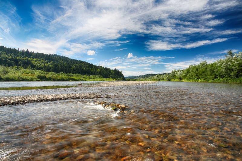Ρεύμα ποταμών βουνών του νερού στους βράχους με το μεγαλοπρεπές μπλε s στοκ φωτογραφία με δικαίωμα ελεύθερης χρήσης
