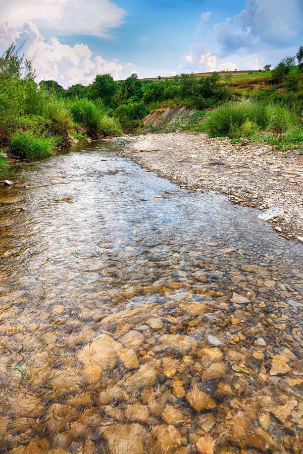 Ρεύμα ποταμών βουνών του νερού στους βράχους με το μεγαλοπρεπές μπλε s στοκ εικόνα