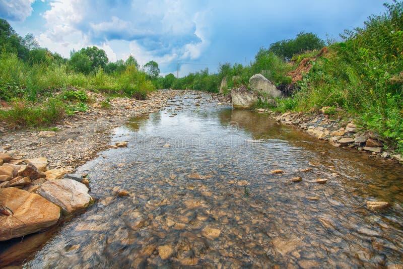 Ρεύμα ποταμών βουνών του νερού στους βράχους με το μεγαλοπρεπές μπλε s στοκ εικόνες