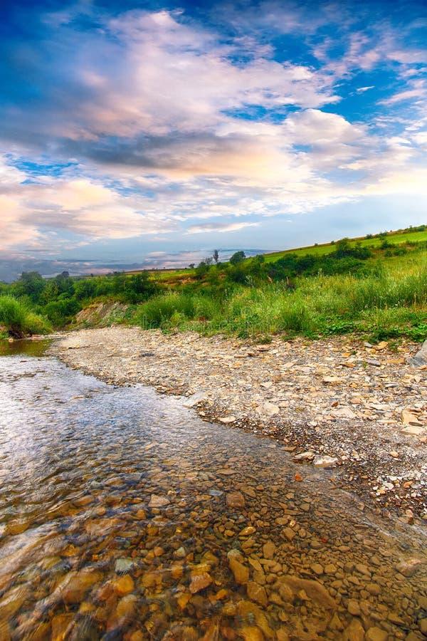 Ρεύμα ποταμών βουνών του νερού στους βράχους με το μεγαλοπρεπές μπλε s στοκ φωτογραφίες