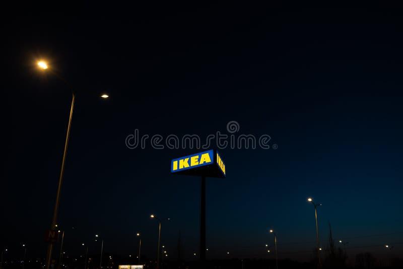 ΡΗΓΑ, ΛΕΤΟΝΙΑ - 3 ΑΠΡΙΛΊΟΥ 2019: Σημάδι εμπορικών σημάτων της IKEA κατά τη διάρκεια του σκοτεινού βραδιού και του αέρα - μπλε ουρ στοκ φωτογραφία