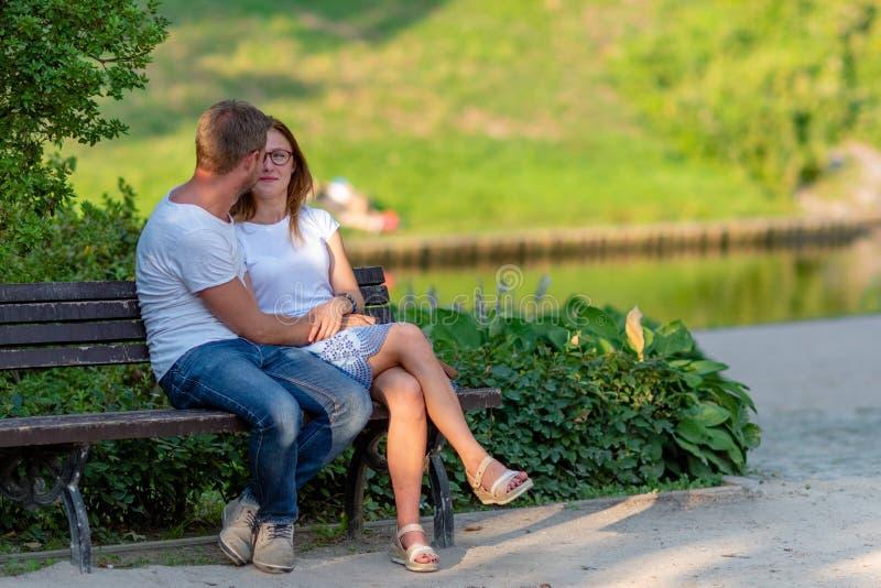 ΡΗΓΑ, ΛΕΤΟΝΙΑ - 26 ΙΟΥΛΊΟΥ 2018: Το αγκάλιασμα των νέων κάθεται σε έναν πάγκο στο πάρκο στοκ εικόνα