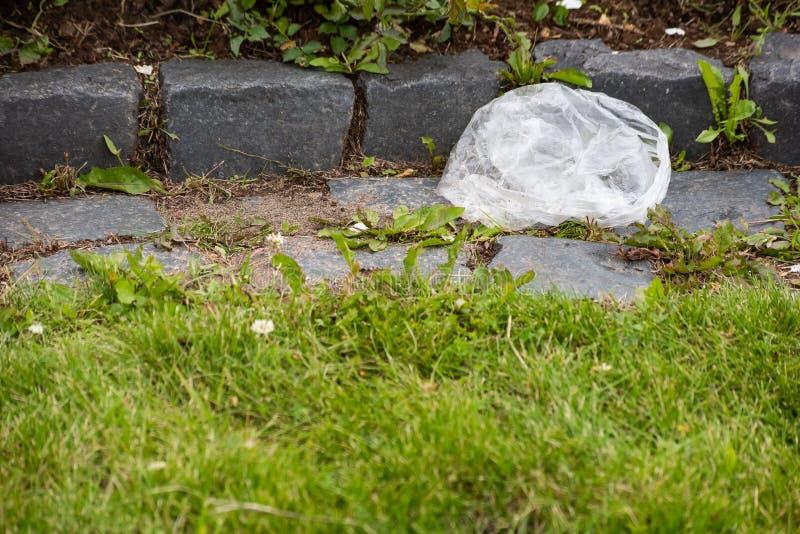Ριγμένη άσπρη τσάντα στην πράσινη χλόη με τη συγκράτηση πετρών στοκ εικόνα