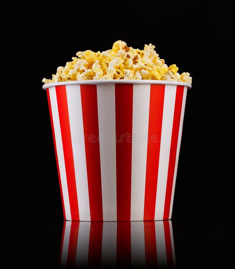 Ριγωτός κάδος εγγράφου με popcorn στο απομονωμένο μαύρο υπόβαθρο στοκ εικόνες