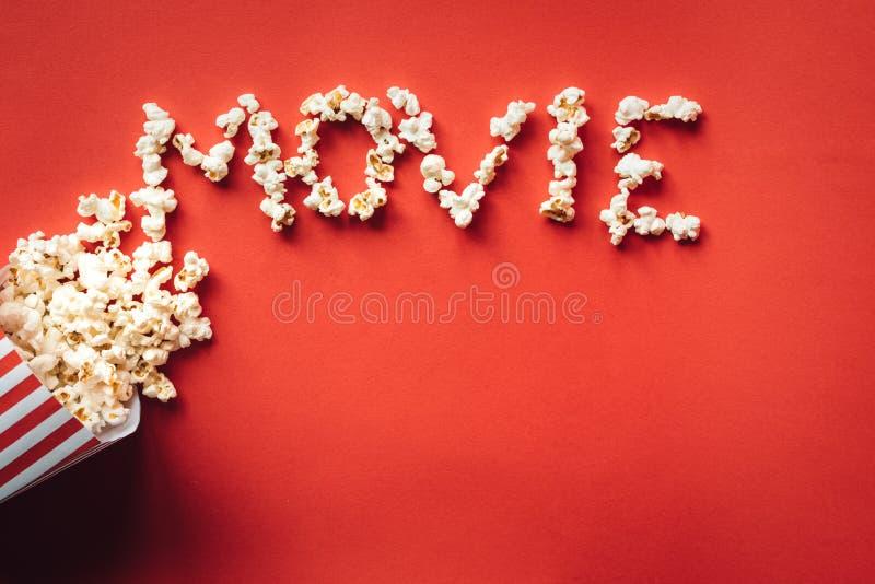 Ριγωτό κιβώτιο με popcorn και λέξης τον κινηματογράφο στοκ εικόνα