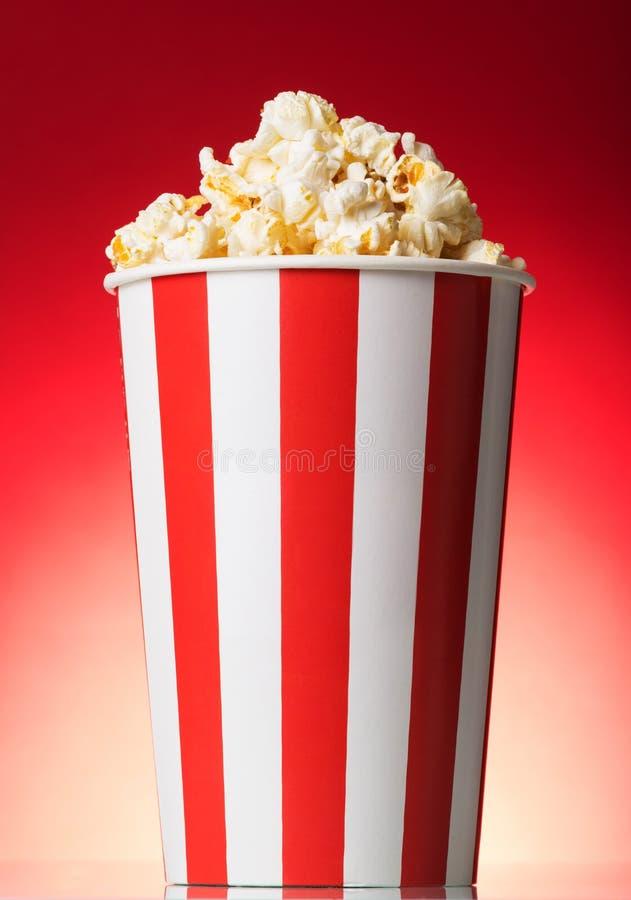 Ριγωτό κιβώτιο με popcorn σε ένα κόκκινο στοκ φωτογραφία