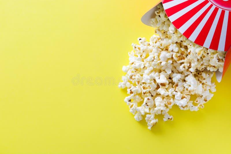 Ριγωτό κιβώτιο με popcorn στο κίτρινο υπόβαθρο Copyspace στοκ εικόνες