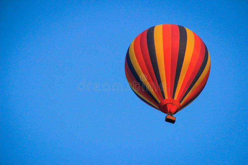 Ριγωτό πολύχρωμο μπαλόνι σε έναν φωτεινό μπλε θερινό ουρανό στοκ εικόνες με δικαίωμα ελεύθερης χρήσης