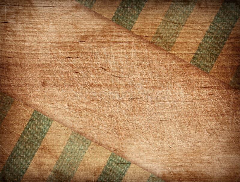 Ριγωτό τραπεζομάντιλο Grunge στον ξύλινο τέμνοντα πίνακα στοκ φωτογραφία με δικαίωμα ελεύθερης χρήσης