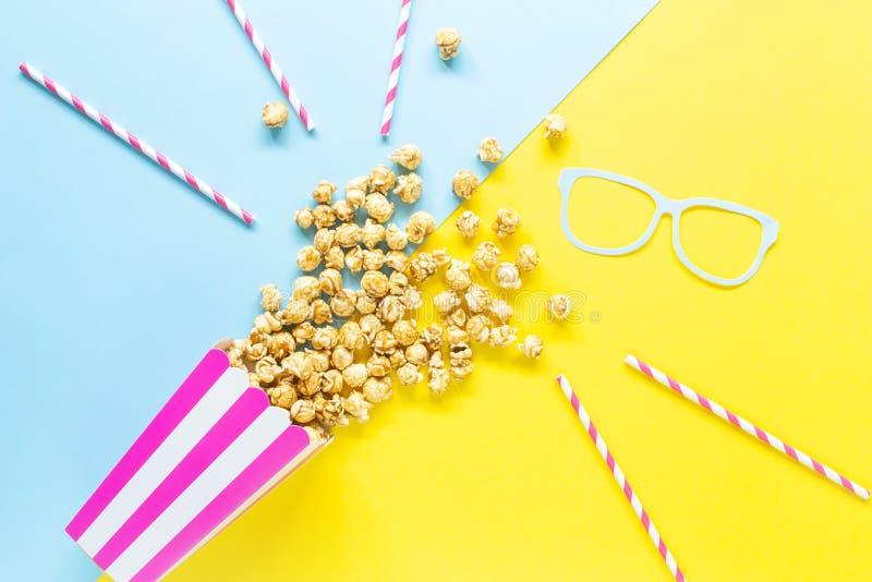 Ριγωτό φλυτζάνι εγγράφου με popcorn στο κίτρινο και μπλε υπόβαθρο στοκ φωτογραφία