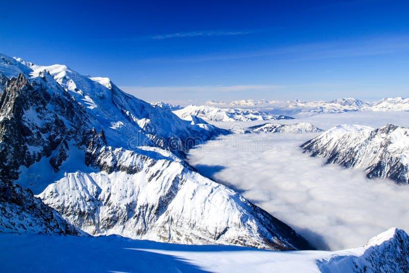 Ροές ομίχλης σε μια χιονώδη κοιλάδα μεταξύ των βουνών στοκ εικόνα