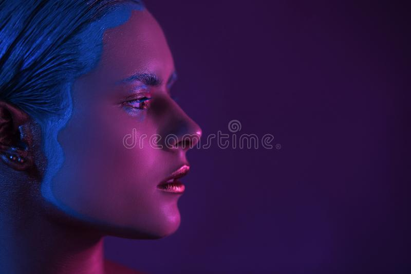 Ροδανιλίνης μισό πρόσωπο του όμορφου προτύπου μόδας νέων κοριτσιών υψηλού στο φως νέου στοκ εικόνες