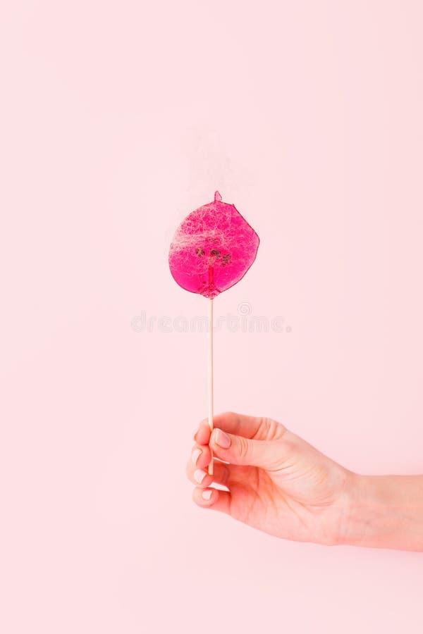 Ροζ γλειφιτζούρι με κολλώδη μαλλιά σε θηλυκό χέρι σε ροζ φόντο Η έννοια του κομμωτηρίου, της αφαίρεσης μαλλιών, της απομνημόνευση στοκ εικόνες